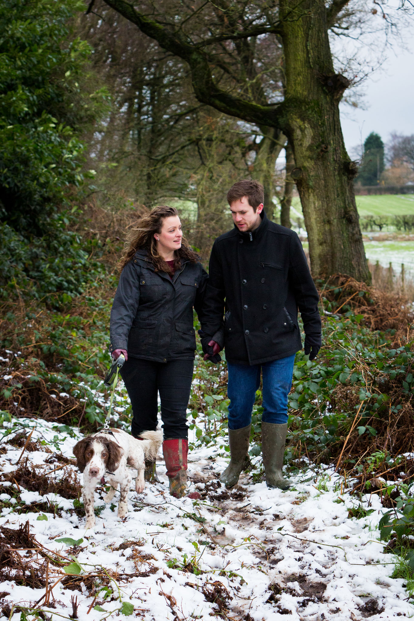 A Portrait of a young couple walking their dog in the snow near Lymm, Cheshire by Cheshire lifestyle photographer Andrew Collier Photography