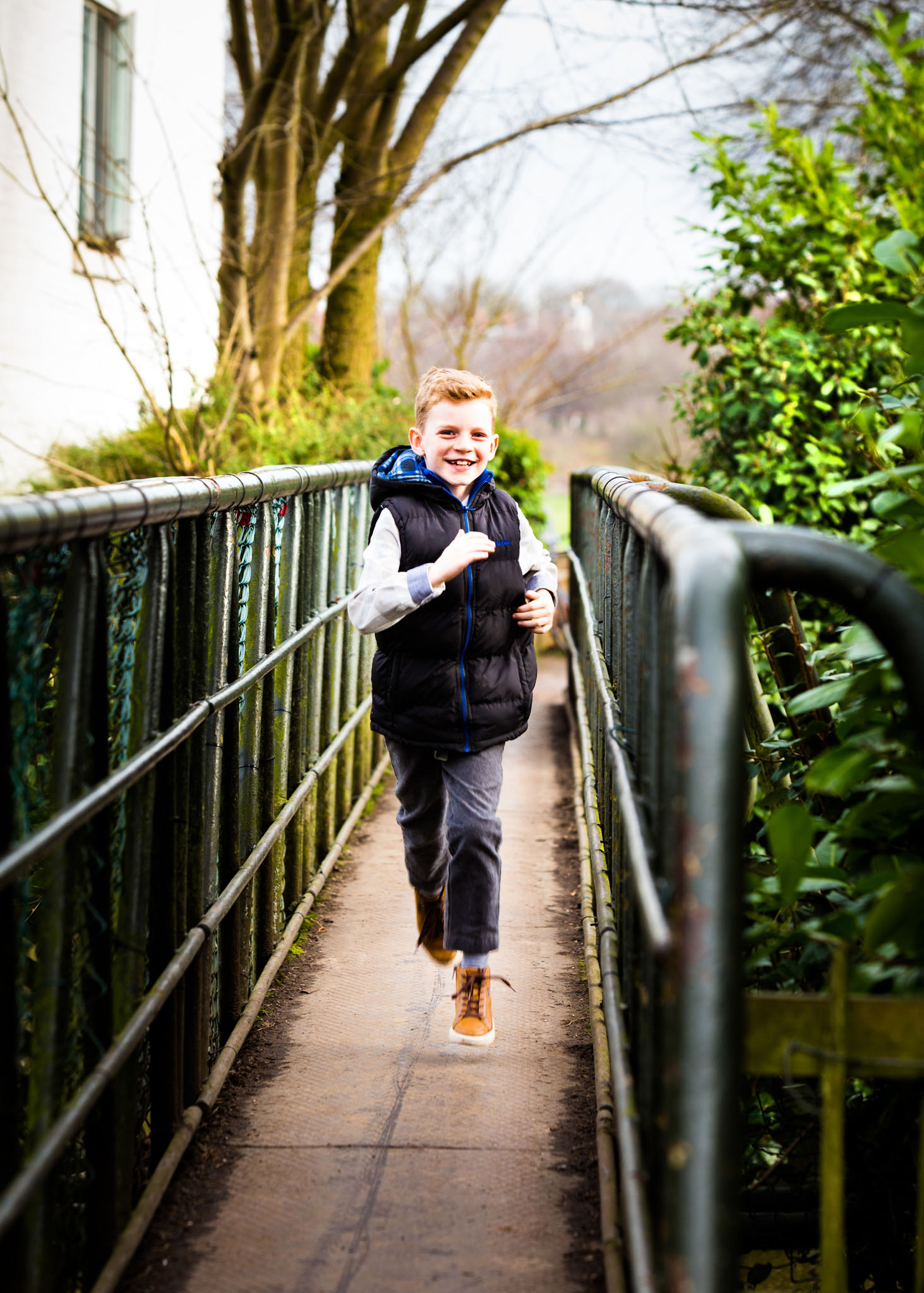 Lifestyle family portrait photography of a young boy running in Dunham, Cheshire