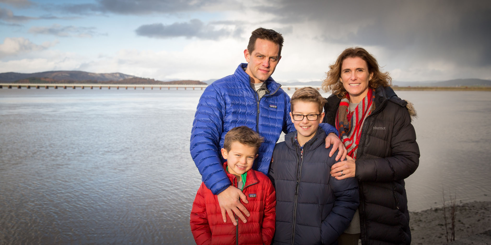 Lifestyle family portrait photography of a young family by the river Kent in Arnside, Cumbria