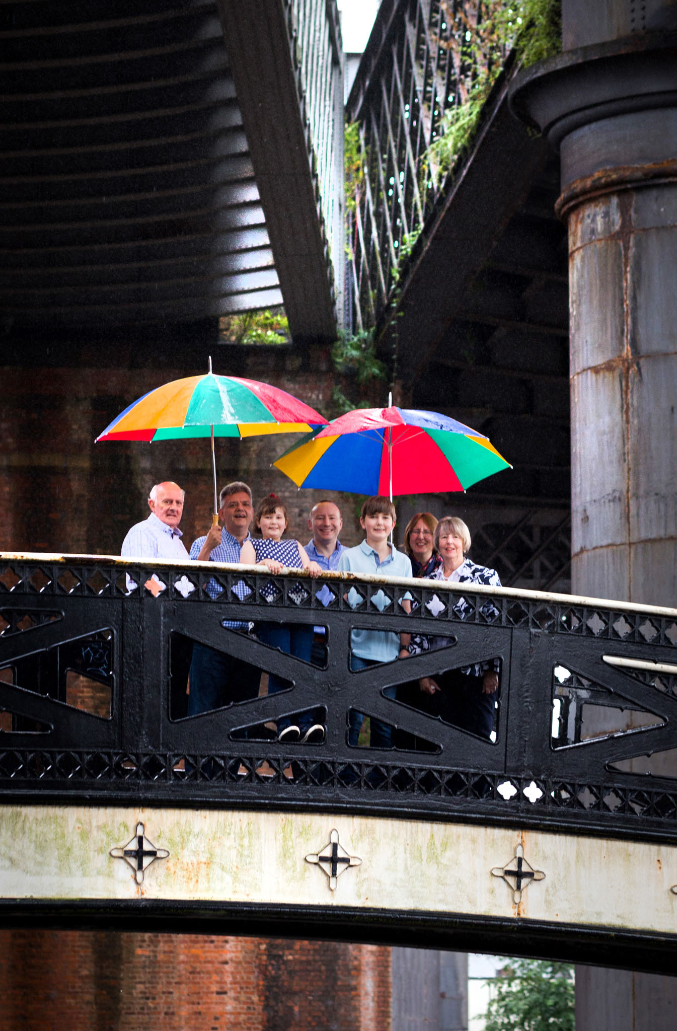 Lifestyle family portrait photography of a family group in the rain in Castlefield, Manchester