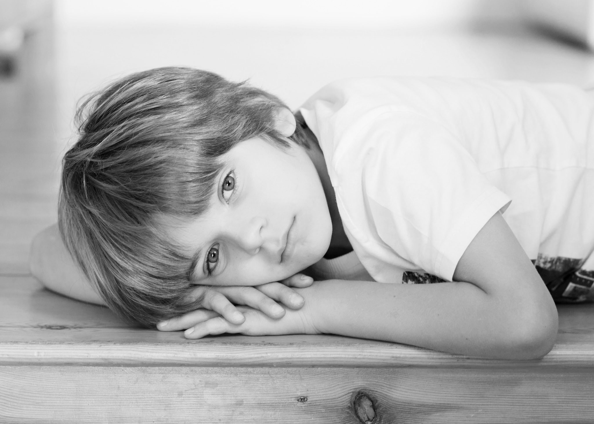 Lifestyle family portrait photography of a young boy lying on the floor in Didsbury, Manchester