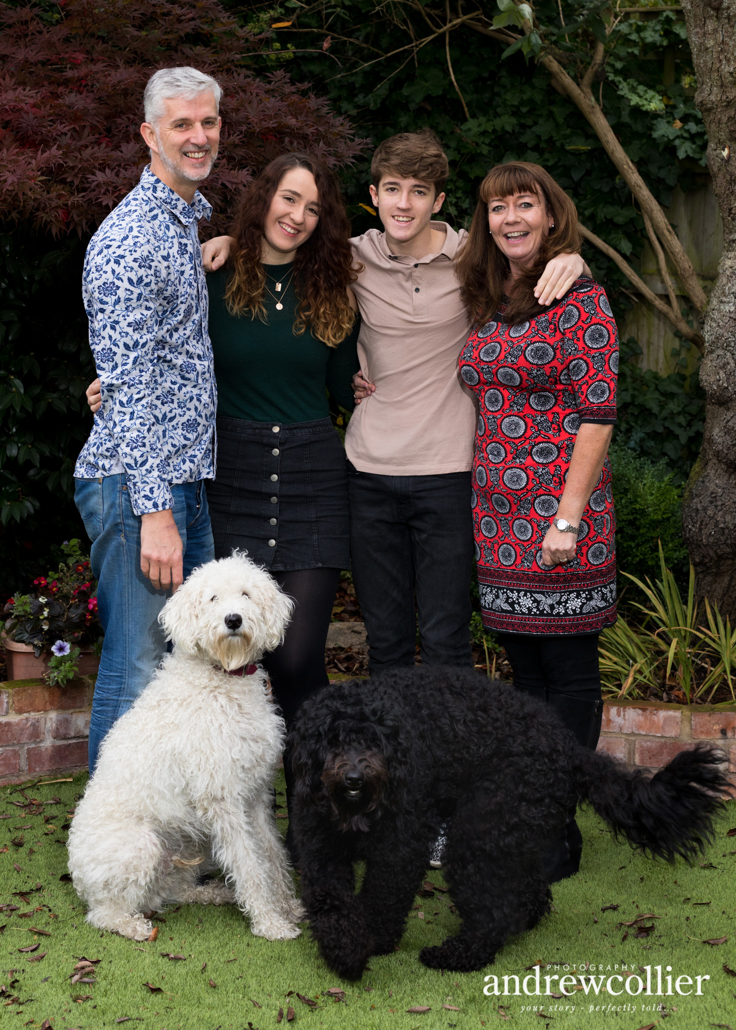 a colour portrait photograph of a mother, father, son and daughter and two labradoodle dogs from a winter family portrait session in Didsbury, South Manchester