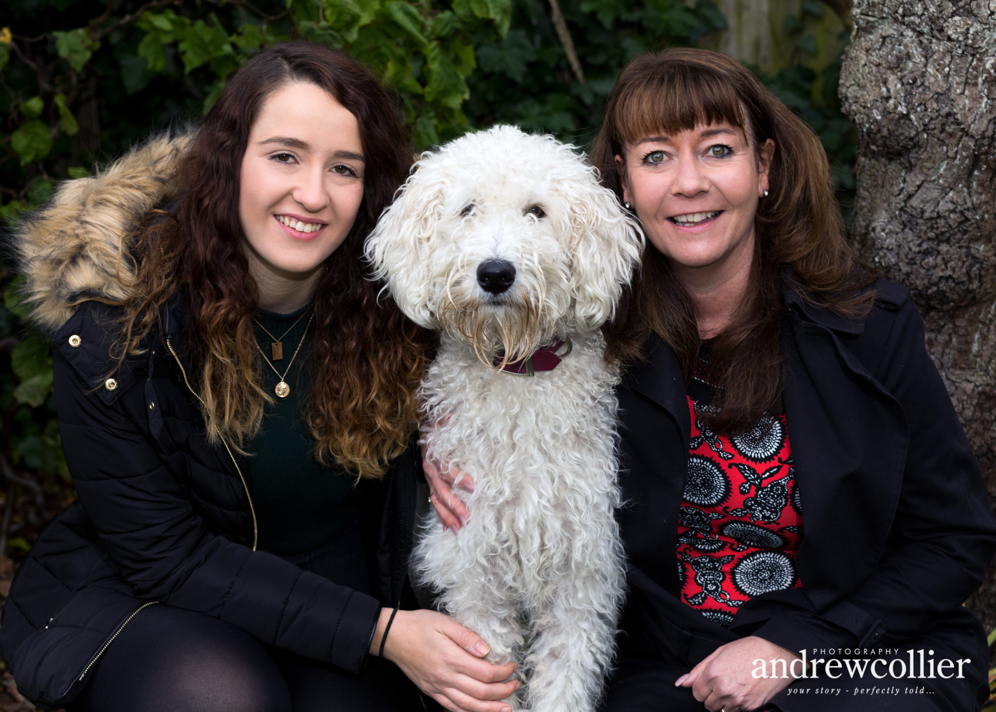 a colour portrait photograph of a mother daughter and a white labradoodle dog from a winter family portrait session in Didsbury, South Manchester