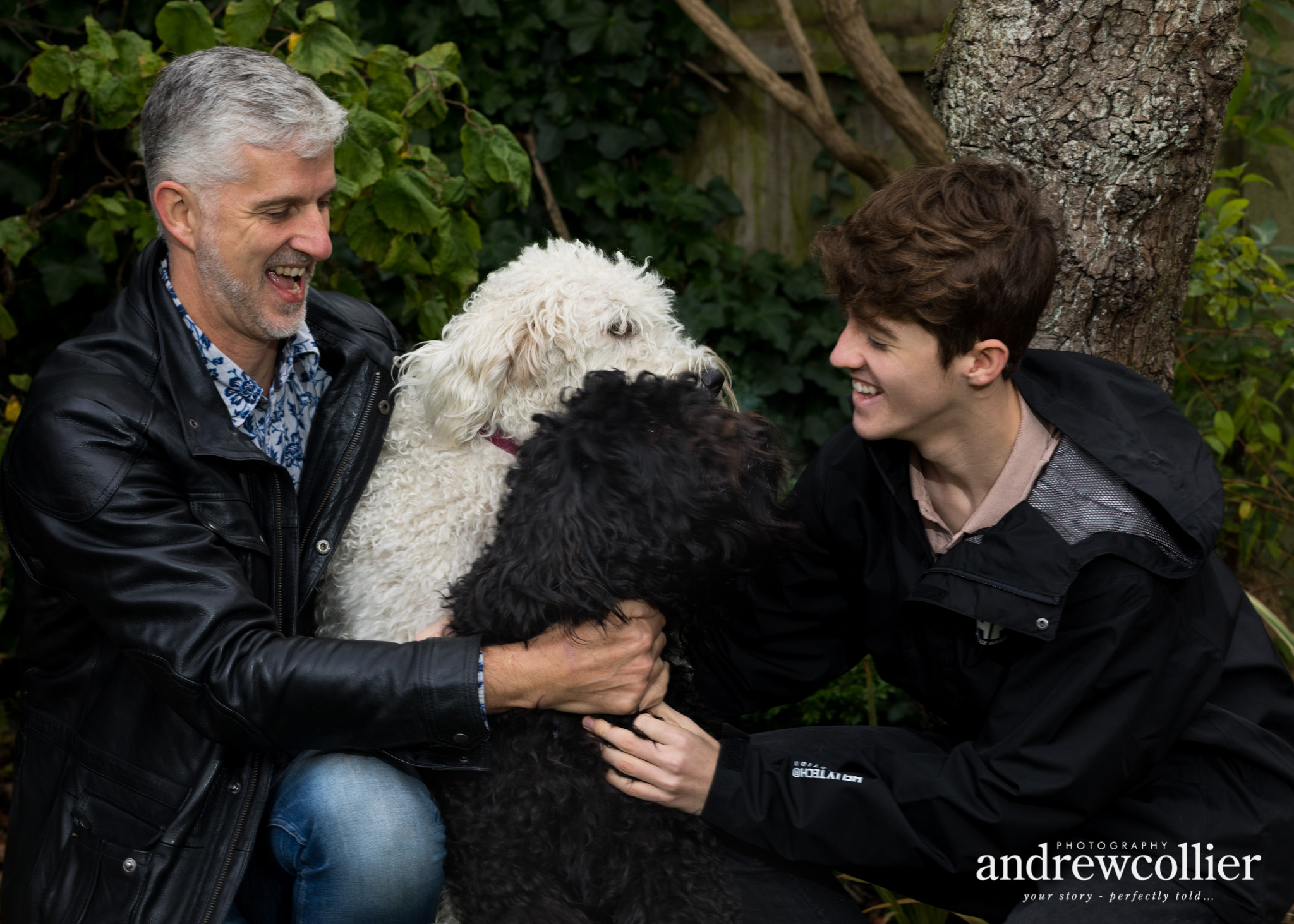 a colour portrait photograph of a father and son with two labradoodle dogs from a winter family portrait session in Didsbury, South Manchester