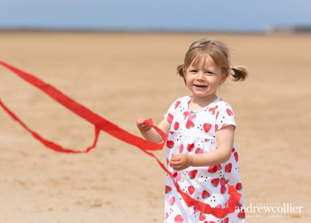 A photograph of a little girl playing with a kite ribbon at West Kirby beach, Wirral, UK