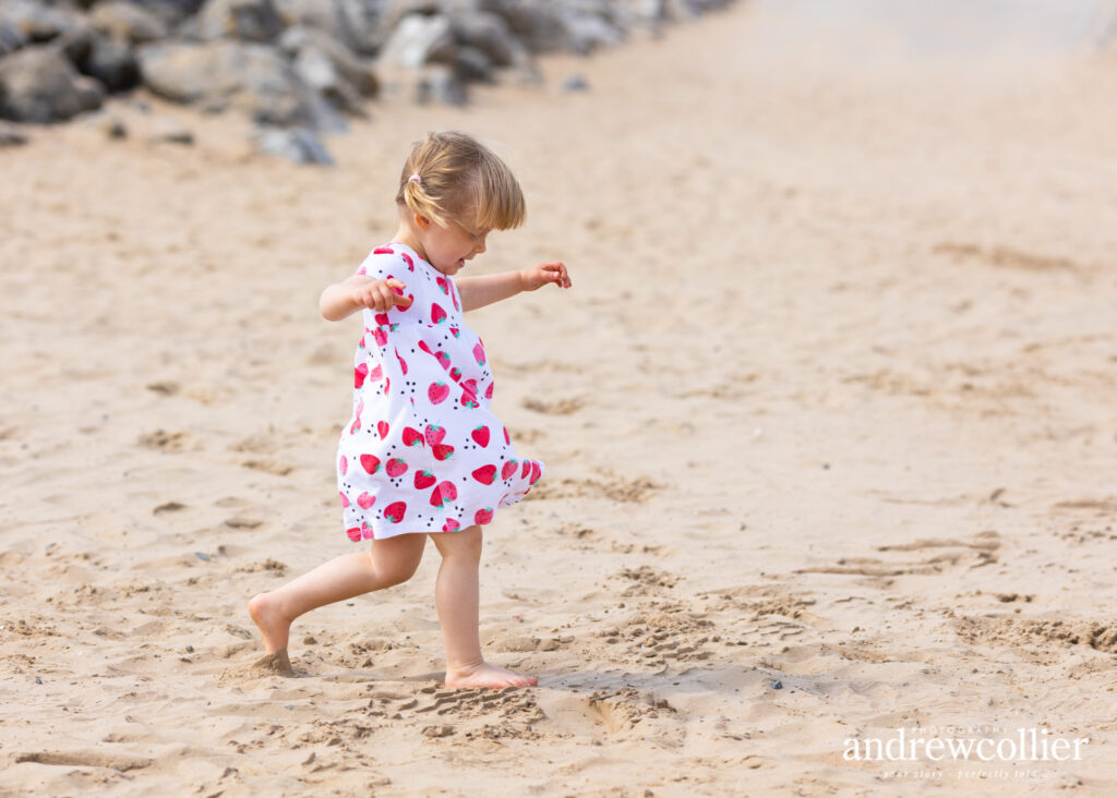 Portrait photograph of young girl running on the sands at West Kirby, Wirral, UK.