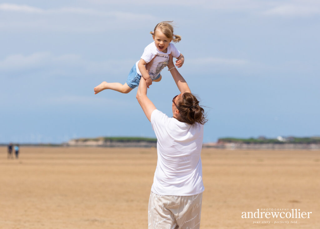 Portrait photograph of mother and daughter playing on the beach at West Kirby, Wirral, UK.